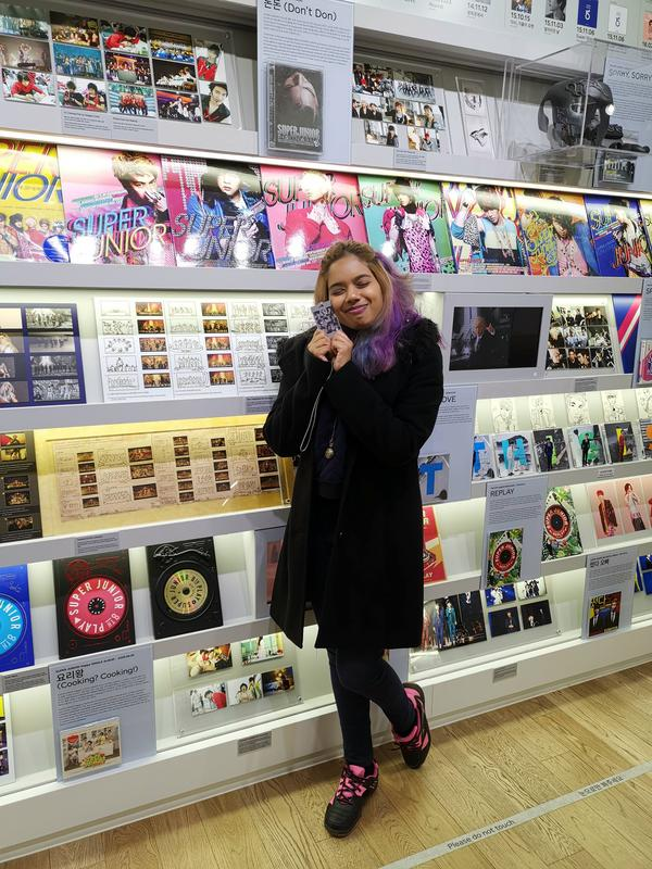 Gowri in front of the History of Super Junior display at the SMTOWN Coex Artium in Seoul.