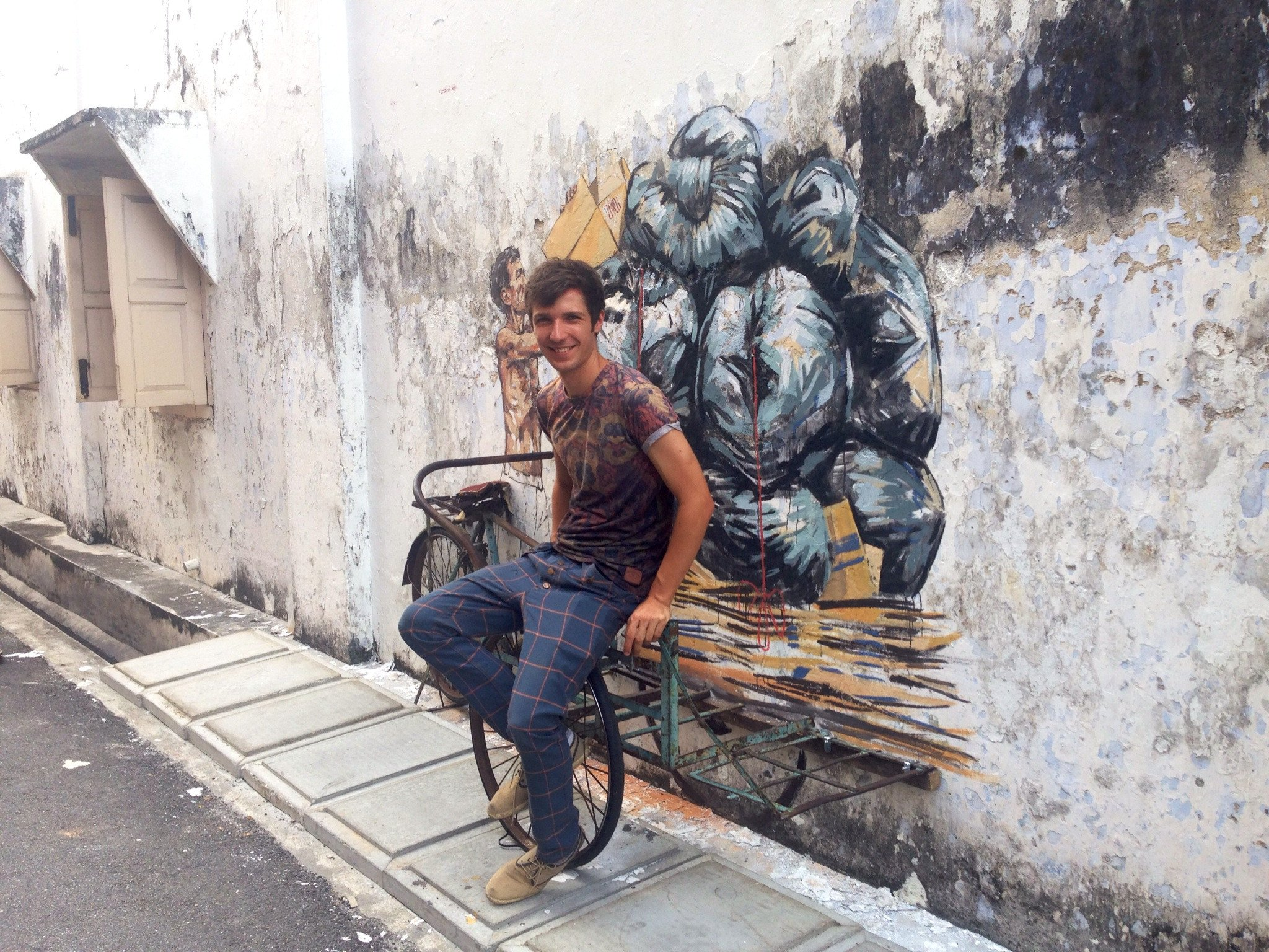 Ernest Zacharevic with one of his murals in Ipoh.