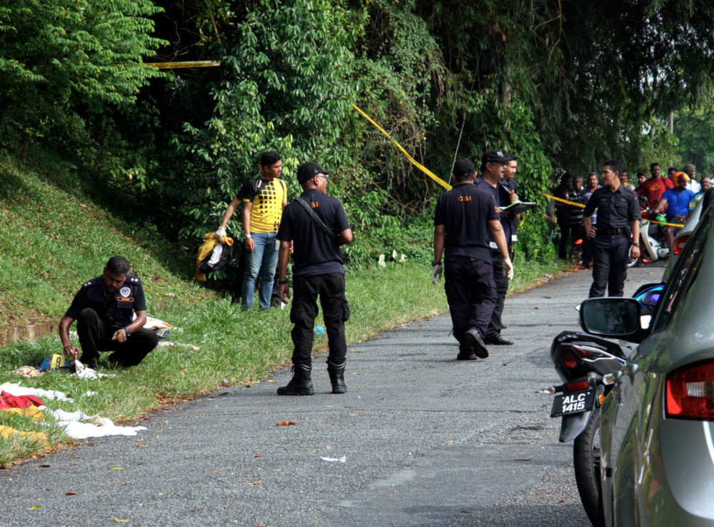 Authorities inspecting the crime scene yesterday after discovering the victim's body.
