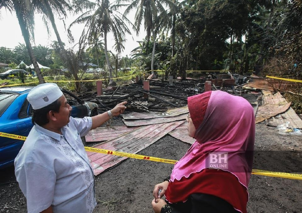 Khamijas Ngainan (left) and his wife (right) in front of the house that burned down.