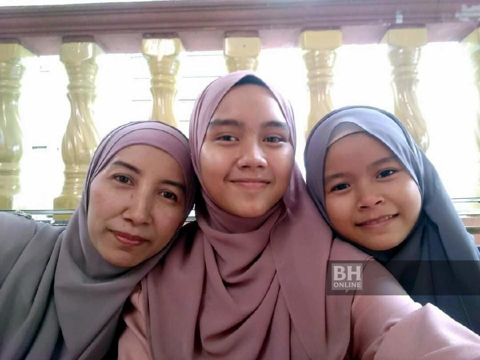 The two teenage girls with their mother Serihati (left).