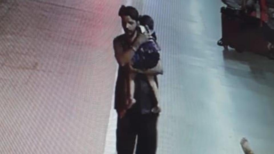 The suspect who can be seen on CCTV footage coolly walking away with the sleeping girl in his arms.