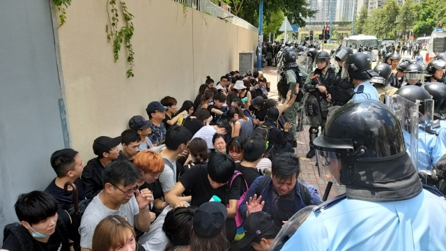 Residents and feminist group protesters are seen surrounded by Tin Shui Wai police on Monday.