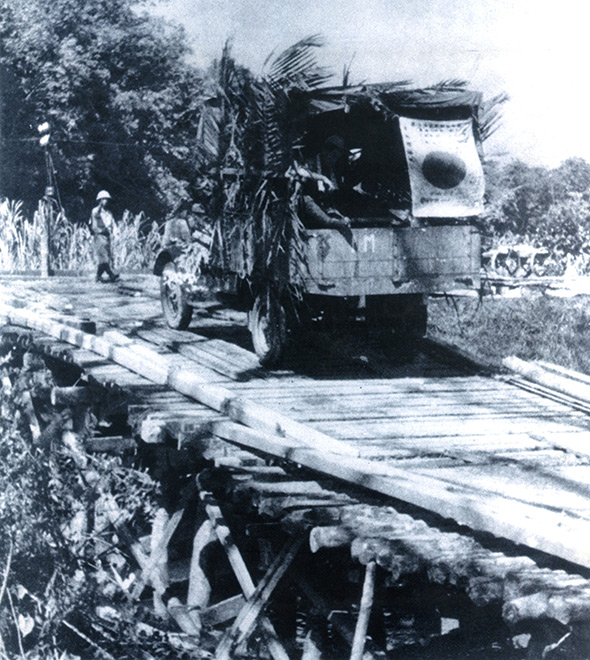 Trucks of the Imperial Japanese Army cross a bridge for an attack on Singapore in December 1941 after landing on the Malay Peninsula.