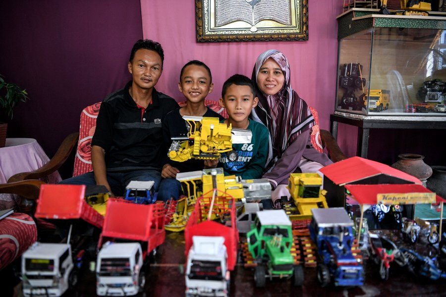 Muhammad Adam (second from left) posing with his other creations alongside his family at their home.