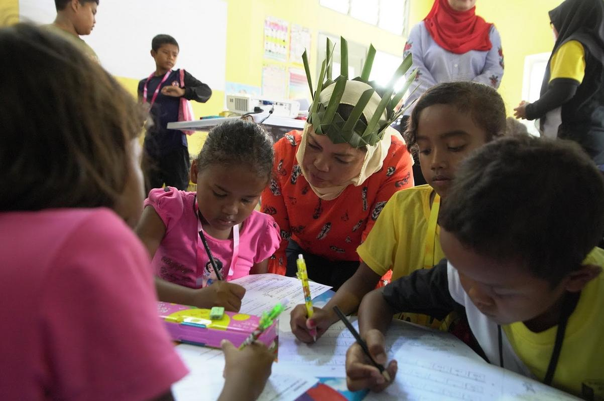 Orang Asli children of Kampung Sungai Cincin learning how to read, write, and count.