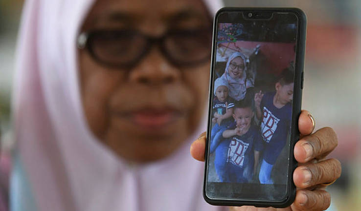 Picture of Surawati Mohd and her three sons.