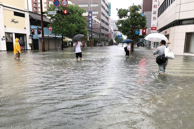 People wading through clear floodwaters in Saga city, Japan.