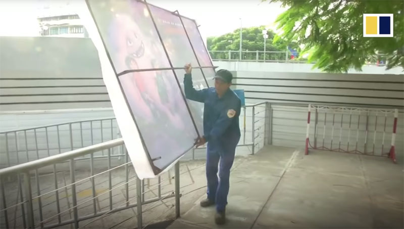 An 'Abominable' poster being removed by a worker in Vietnam.