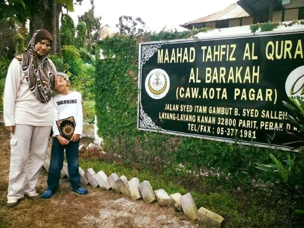 The mother with her son in front of Maahad Tahfiz al Barakah, the tahfiz school in Manjoi where the boy was allegedly sexually abused. The tahfiz school was formerly owned by celebrity preacher Datuk Kazim Elias.