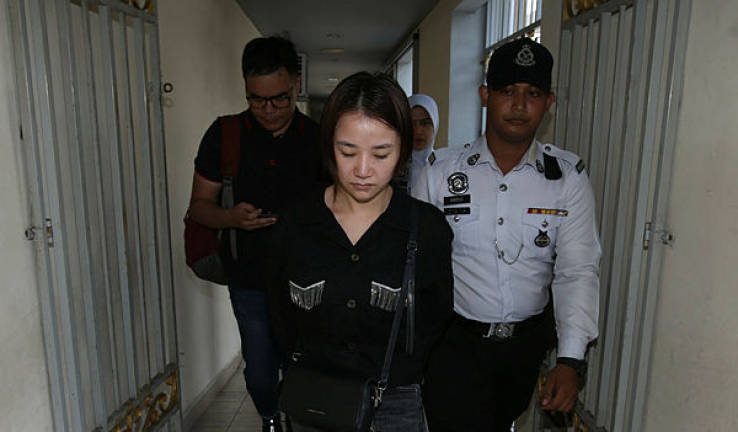 Liu Shasha accompanied by police at the Magistrate's Court in George Town yesterday
