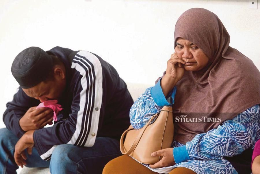 Aimin's father, Nurul Amin Abdul Rahman, and stepmother Hasmaliza AhmadNurul grieving.