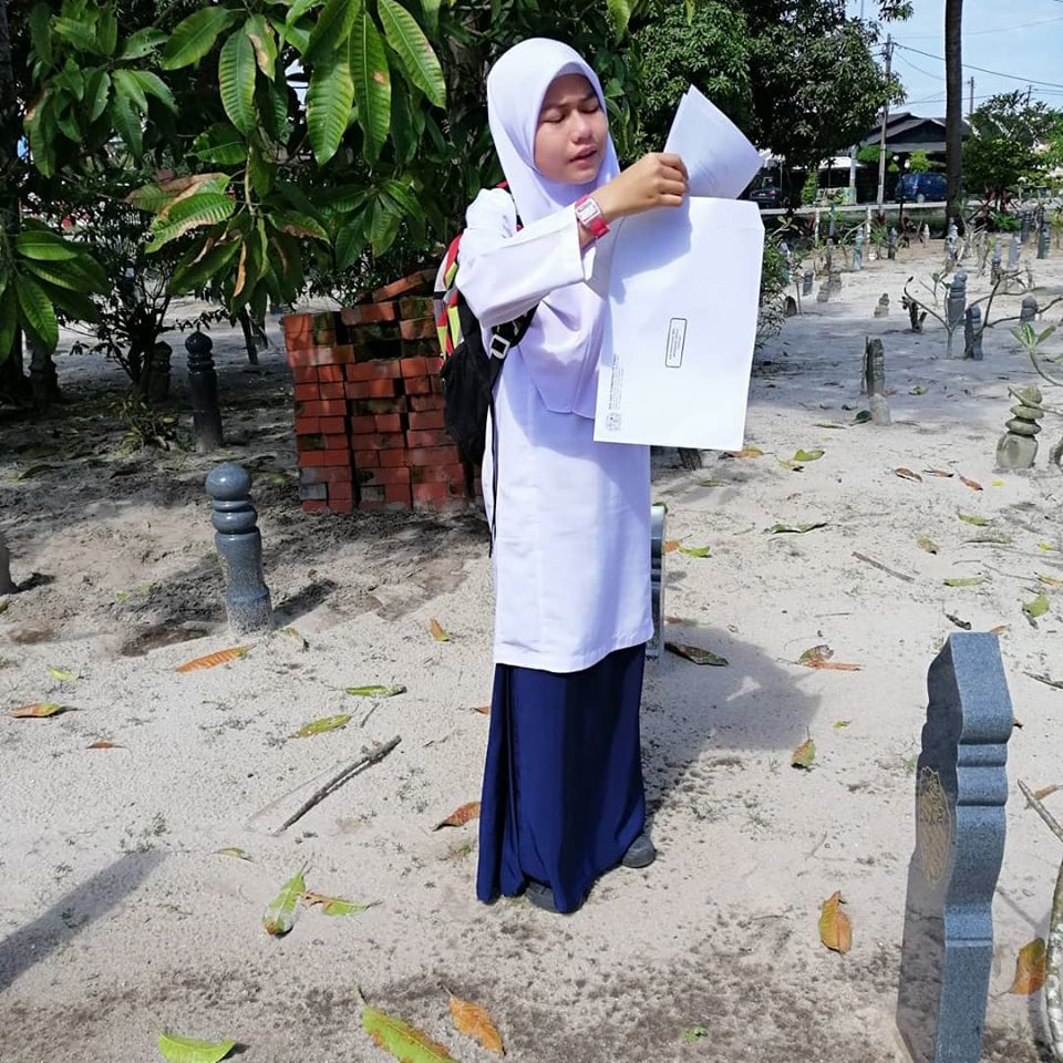 Aqilah reciting what she received for each subject in front of her mother's tombstone.