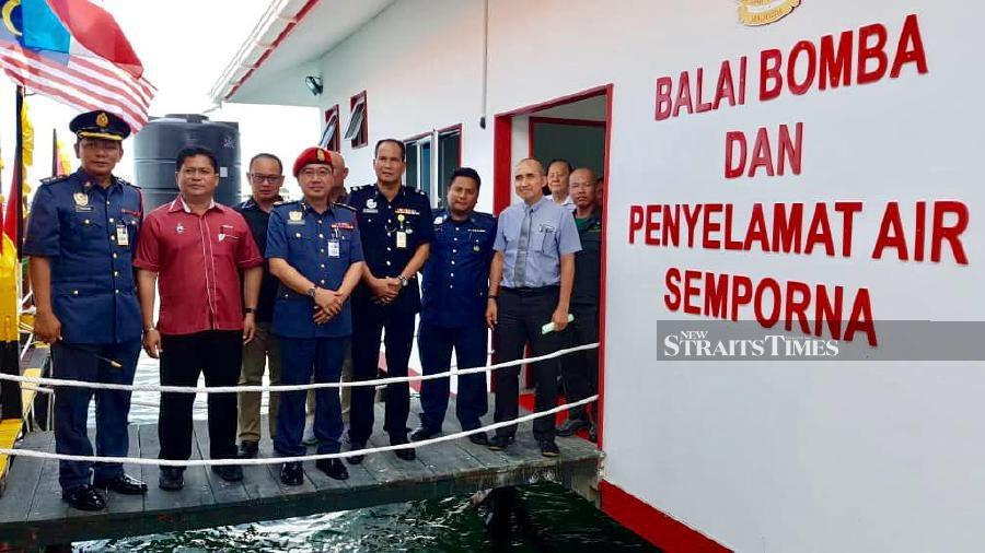 Sabah Fire and Rescue department director Kamarulzaman Malik Abdullah (centre) poses for a group photo at the floating fire station in Semporna.