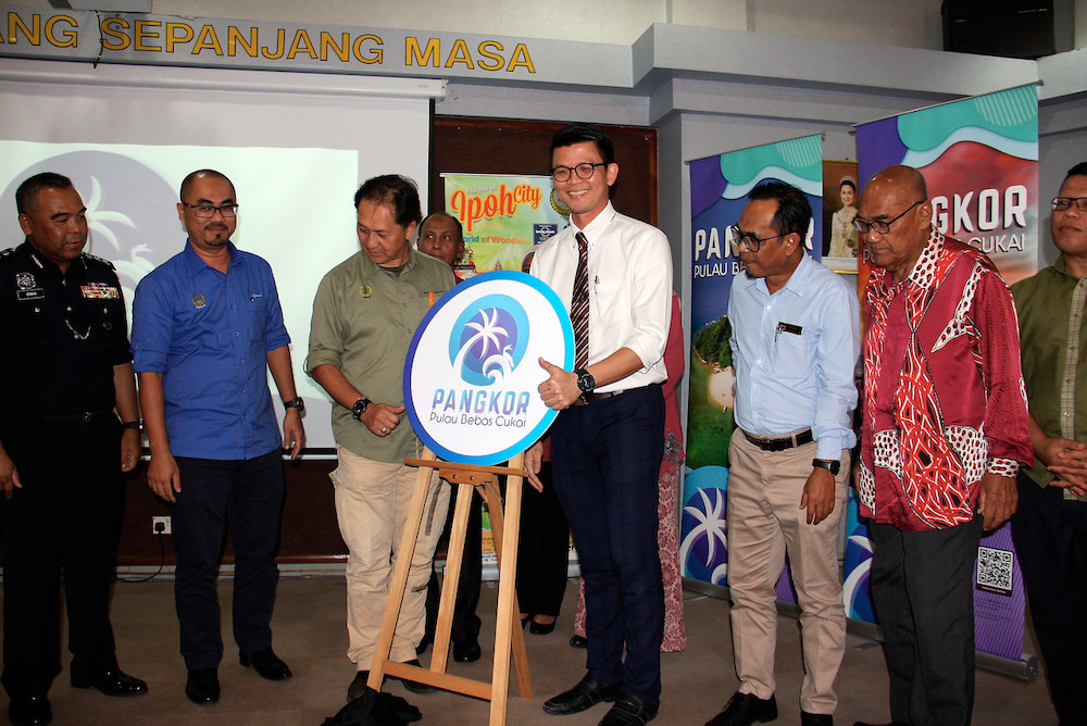 Tan (third right) and Perak Secretary Zainal Azman Abu Seman (third left) during the launch of a new logo for Pangkor Island.