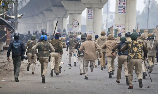 Police chase protesters following the passage of new citizenship law in New Delhi, India, on 17 December 2019.