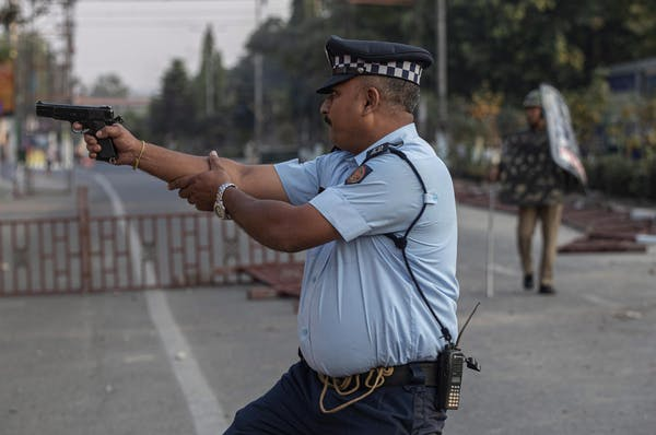 An Indian cop aims his gun before firing at stone-throwing protesters in Gauhati, India, on 12 December. No one was hurt.