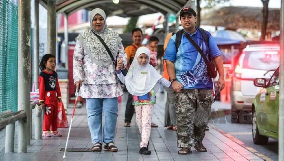 Nur Khairunnisa with her visually-impaired parents, Nur Suhaida and Mohammad Haizir.