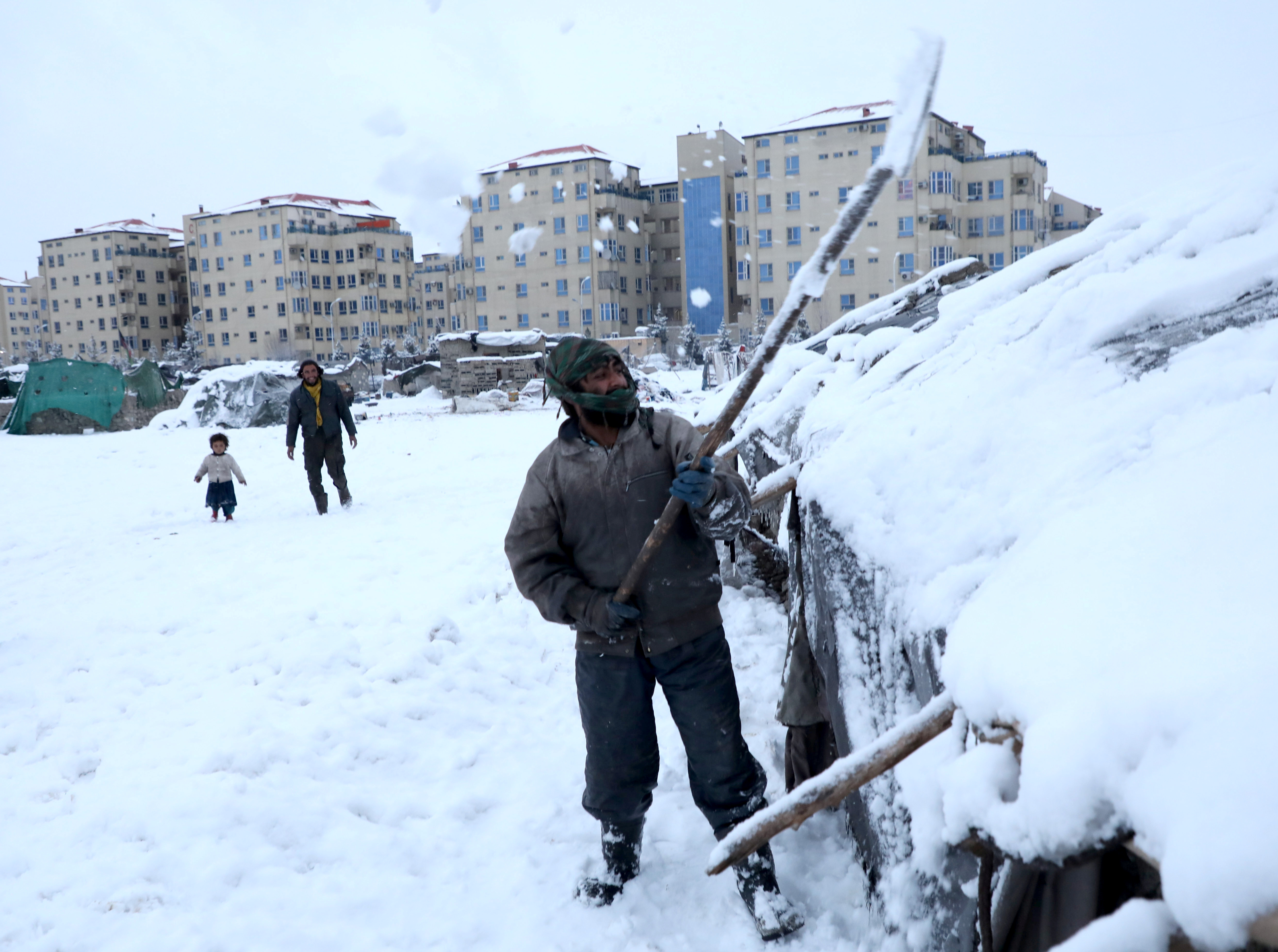 An Afghan man removes snow from his shelter in Kabul, Afghanistan 12 January 2020.