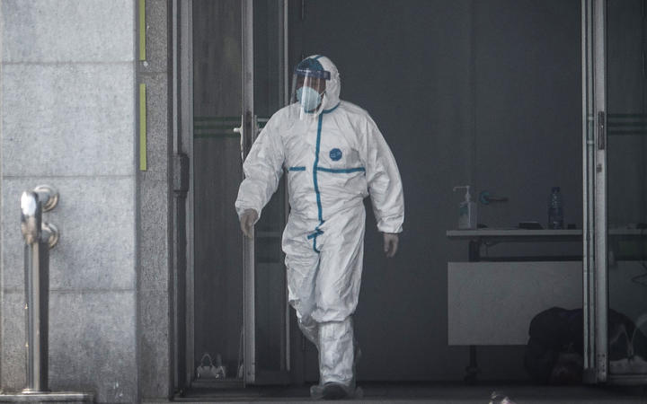 A medical staff member walks outside the Jinyintan hospital, where patients infected with the coronavirus are being treated.