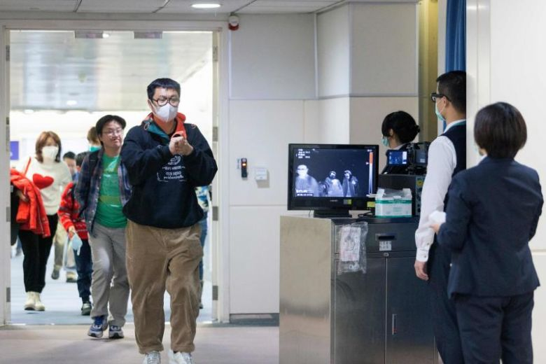 Taiwan's Centres for Disease Control personnel using thermal scanners to screen passengers arriving from Wuhan at Taoyuan Internation Airport in Taipei.