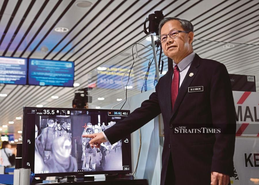 Dr Lee showing a thermal scanner to screen travellers at KLIA, Sepang.