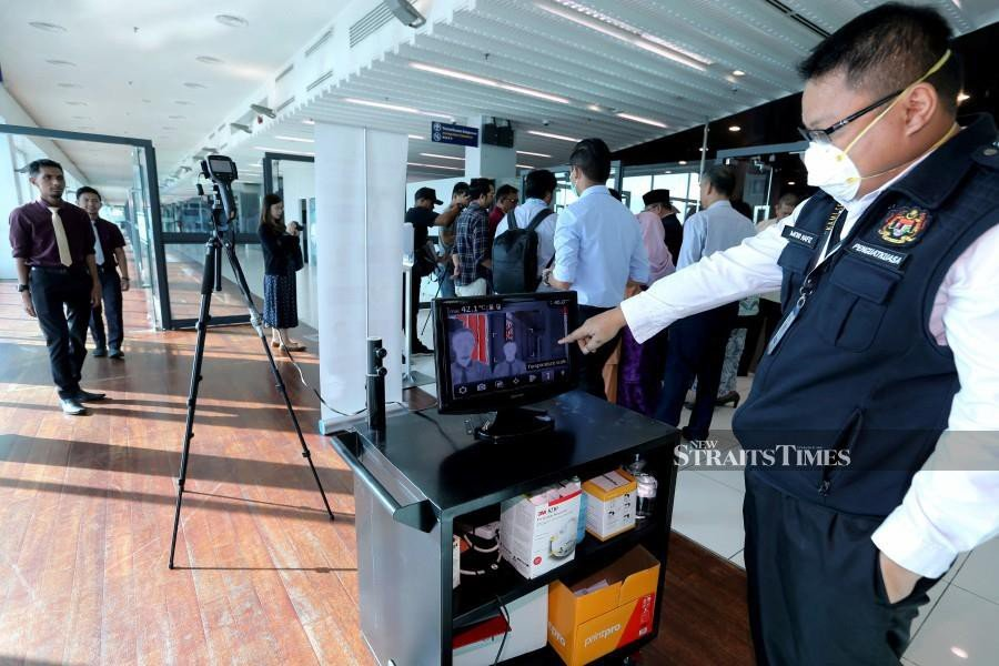A Health Ministry staff observes a thermal scanner installed at the Senai International Airport.