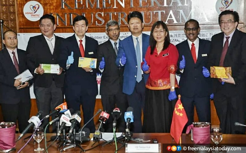 Teresa Kok (third from right), China's ambassador to Malaysia Bai Tian (fourth from right), and representatives of medical glove manufacturers showing samples of the gloves that will be sent to Wuhan, China.