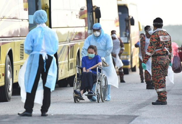 In this image dated 4 February, a health official is seen wheeling a woman to a bus as she and other Malaysian citizens arrive at KLIA in Sepang after being evacuated from Wuhan, the epicentre of the outbreak.