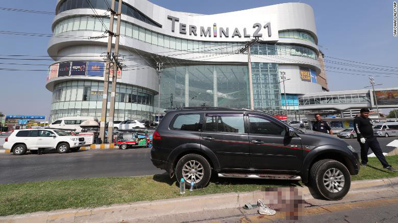 Thai rescue teams walking pass a victim's vehicle outside Terminal 21 mall.