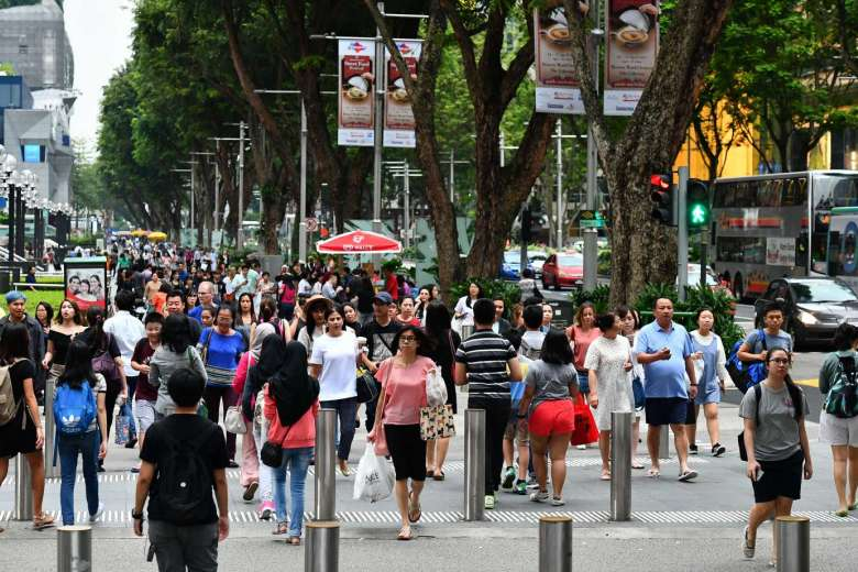 Pedestrians crossing at the junction of Orchard Link and Orchard Road in Singapore.