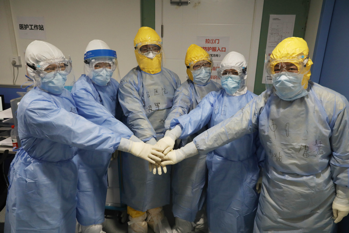 Medical workers joining hands before entering isolation units at Tongji Hospital in Wuhan on 3 February.