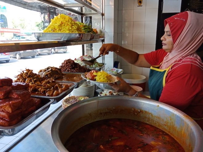 A worker serving nasi kandar.