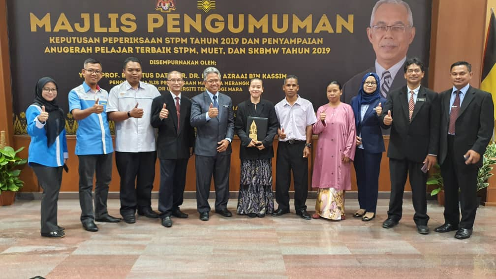 Aimi Mahad (middle, with award) with her parents (on her left).