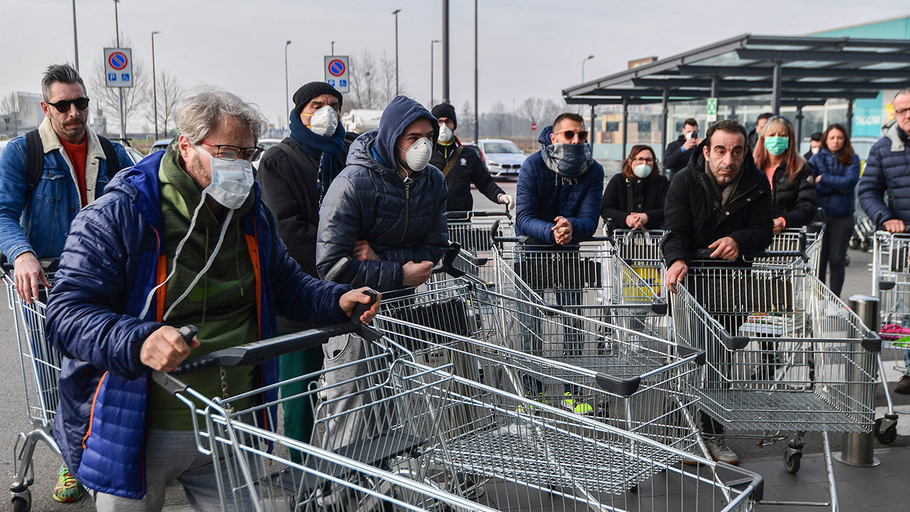 Residents of Casalpusterlengo, an Italian town under lockdown over COVID-19, line up to enter a supermarket.