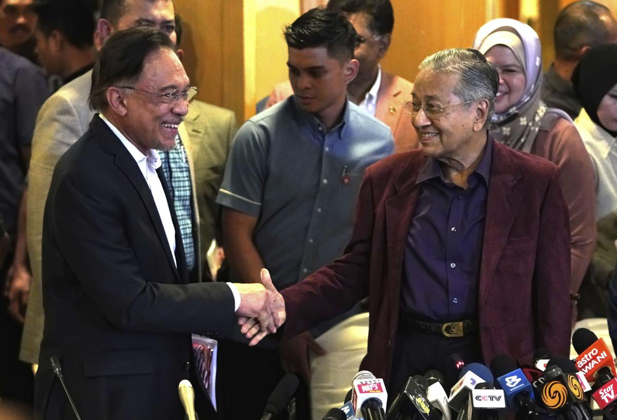 Dr Mahathir shakes hand with Anwar in Putrajaya on 22 February.