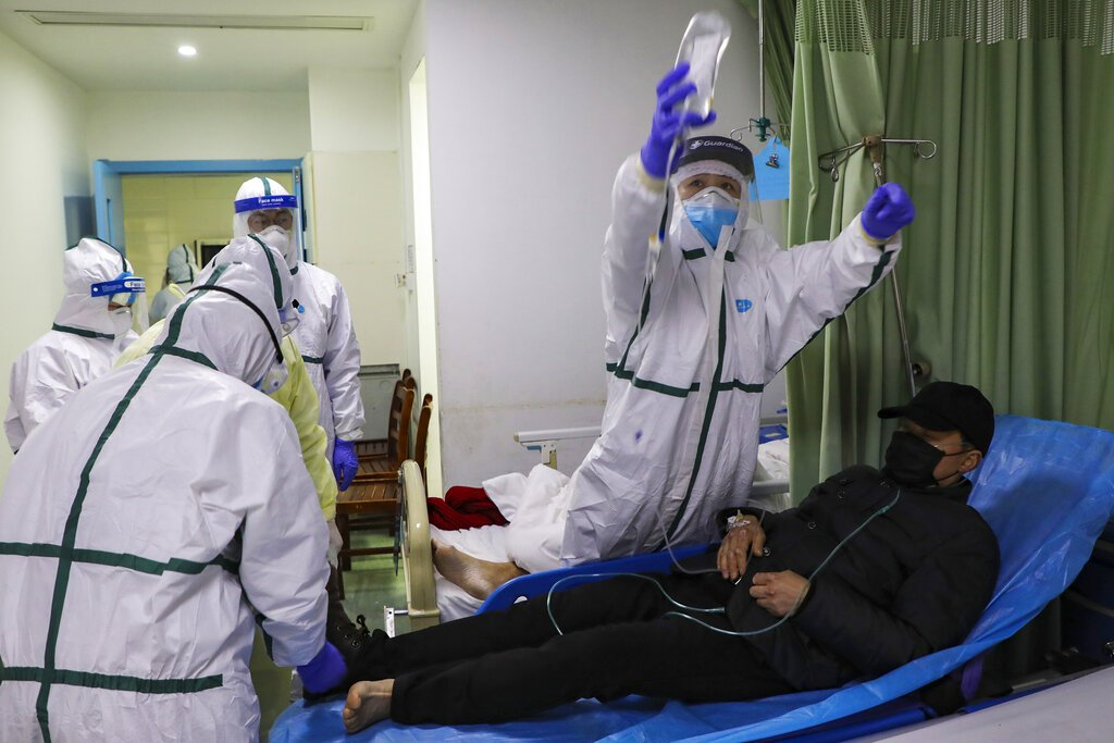 Medical workers prepare to move a man into an isolation ward at a hospital in Wuhan.