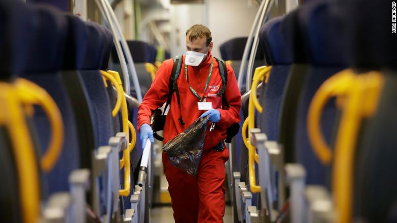 A worker sanitises a car on a regional train in Milan on Friday, 28 January.