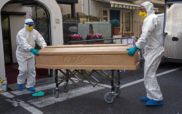 Medical staff wearing protective suits carry the coffin containing the body of a woman after she passed away in her room at the Garden hotel in Laigueglia, northwest Italy, on 1 March.