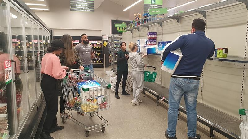 Shoppers in front of almost bare toilet paper shelves in a departmental store in Australia.