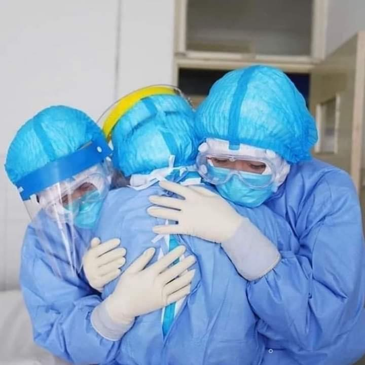 Hospital staff consoling each other.
