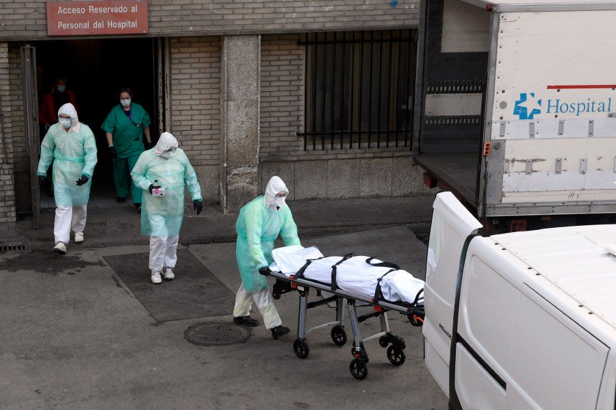Health workers carry a body on a stretcher outside Gregorio Maranon hospital in Madrid, Spain.