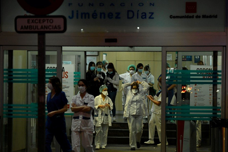 Healthcare workers dealing with the coronavirus crisis at the entrance of the Fundacion Jimenez Diaz hospital in Madrid.