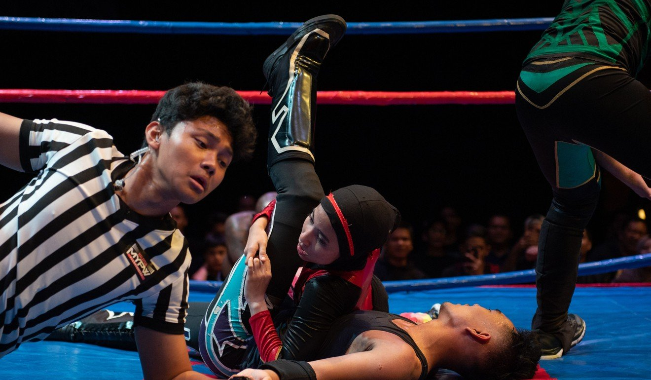 Nor Diana wrestling with a male opponent during a match in KL.