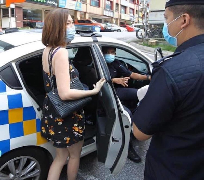 A woman being arrested after she shouted and called police personnel 'idiots' while they were manning an MCO roadblock along Persiaran Surian on Tuesday, 31 March.