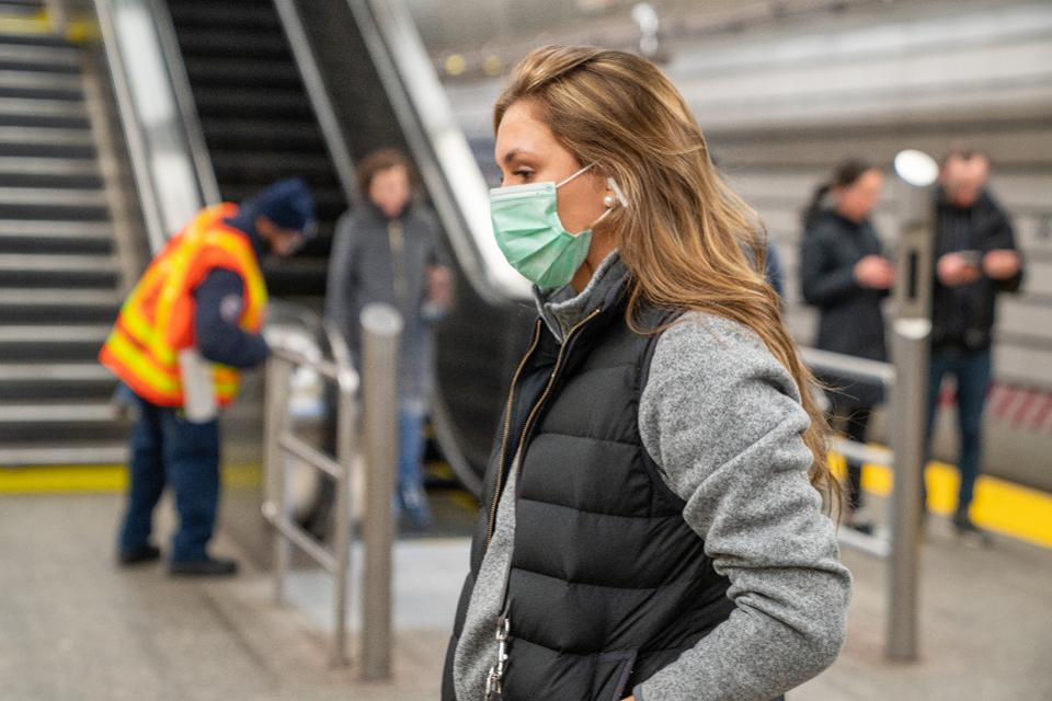 A commuter wearing a protective mask walks a subway station in New York City.