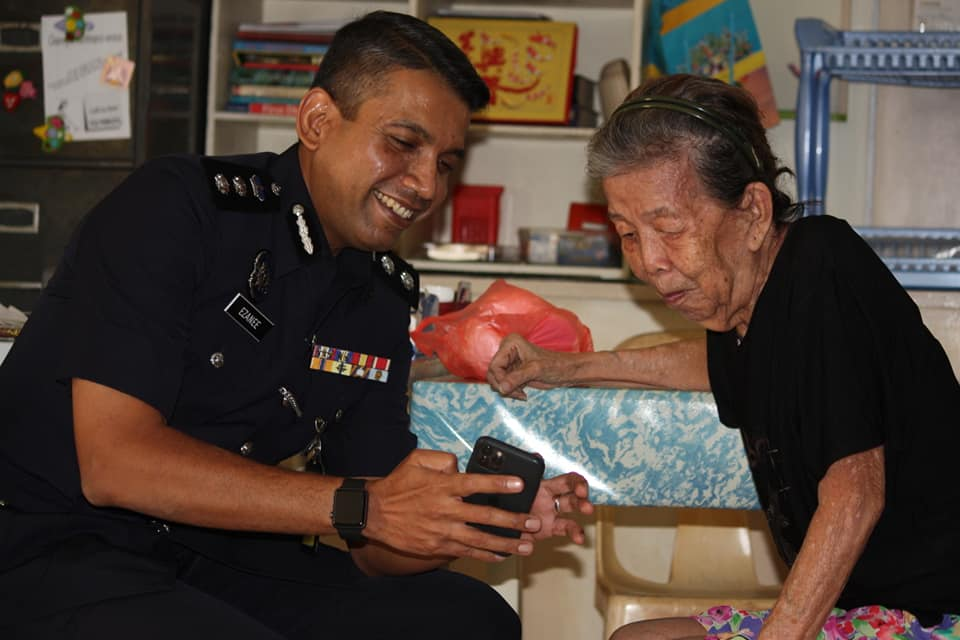 Nik Ezanee sharing pictures of his family members with Ah Siong.