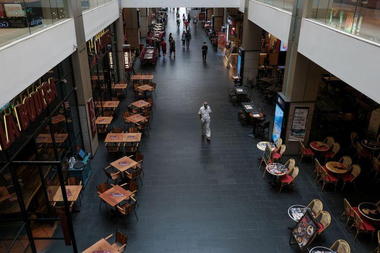 A man wearing a face mask walks through an unusually empty shopping mall in Kuala Lumpur.