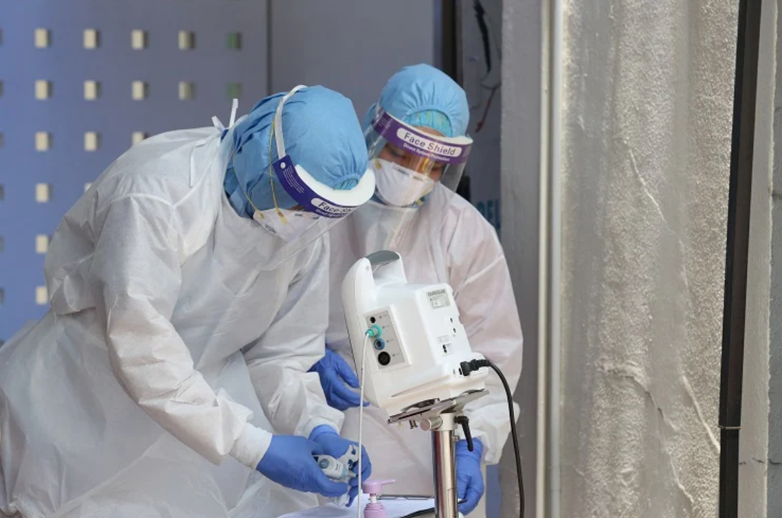 Healthcare workers wearing personal protective equipment (PPE), including the N95 mask.
