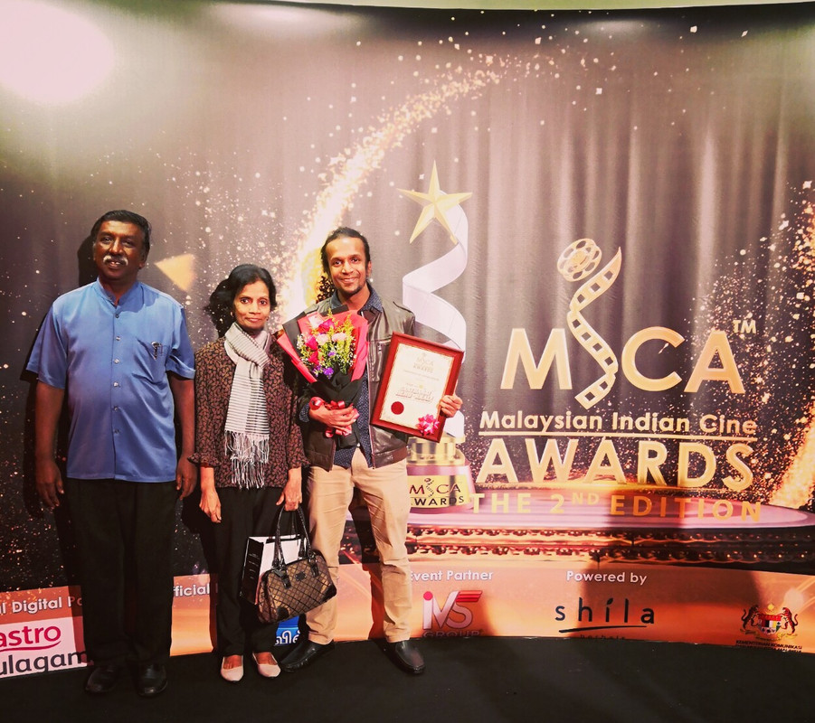 Jeshurun standing with his parents after winning in the 'Unsung Heroes' category at the Malaysian Indian Cine Awards 2019.